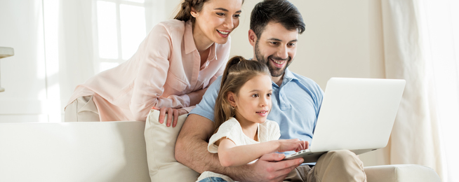 Rodzina z uśmiechami kupuje meble w internecie, siedząc na kanapie w salonie
