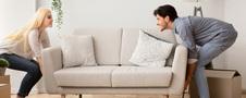 Szczęśliwa para młodych ludzi urządza tanio mieszkanie, przenosi białą kanapę w salonie z uśmiechem