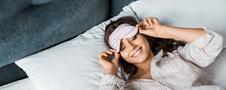 Uśmiechnięta kobieta budzi się w pościeli na łóżku kontynentalnym