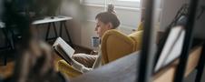 Młoda kobieta czyta ciekawą książkę na żółtym fotelu uszaku w salonie